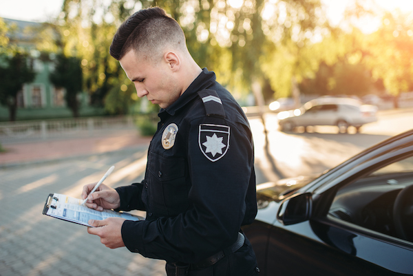 policeman taking notes on a road