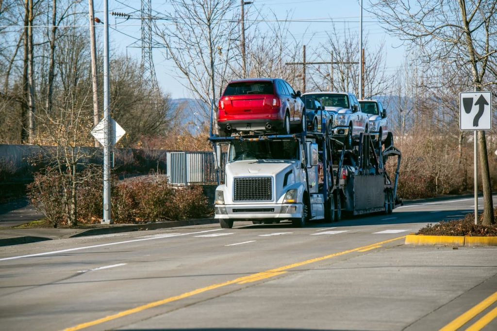 truck-hauling-two-levels-of-cars-on-two-lane-road-in-forested-area