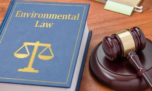 Environmental law book containing emissions laws on a wooden desk beside gavel